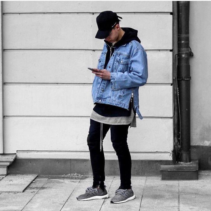 denim jacket paired with black jeans and hoodie gray sneakers streetwear clothing man standing on sidewalk