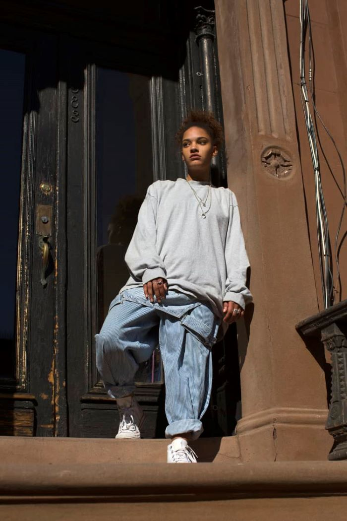 denim overalls gray oversized hoodie worn by woman mens urban clothing standing on staircase