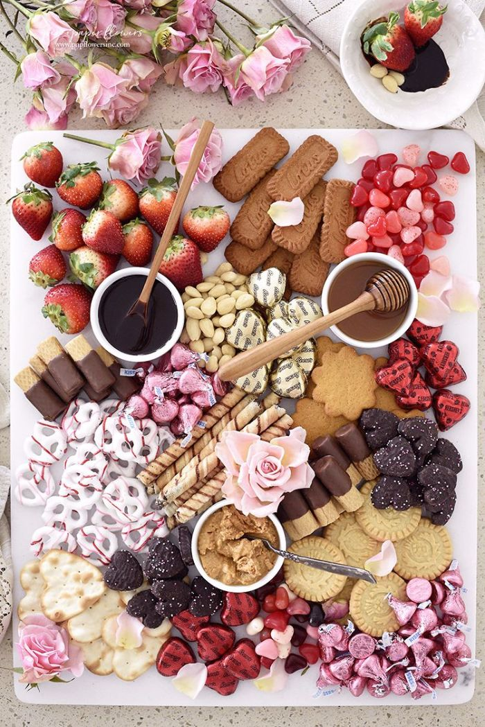 dessert charcuterie board ideas with cookies chocolate crachers strawberries candy arranged on white plate