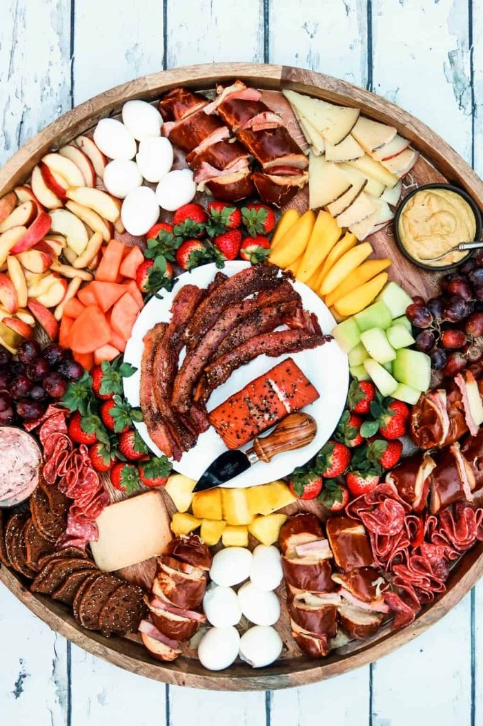 different types of cheese fruits and meet arranged in round charcuterie board made of wood
