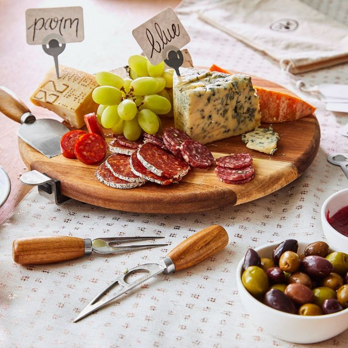 different types of cheese meat grapes on small round wooden board how to make a charcuterie board cheese knives next to it