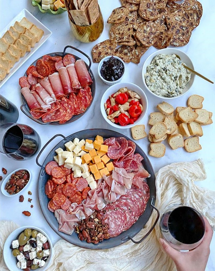 different types of meat and cheese arranges on two round trays charcuterie board ideas condiments and bread on the side