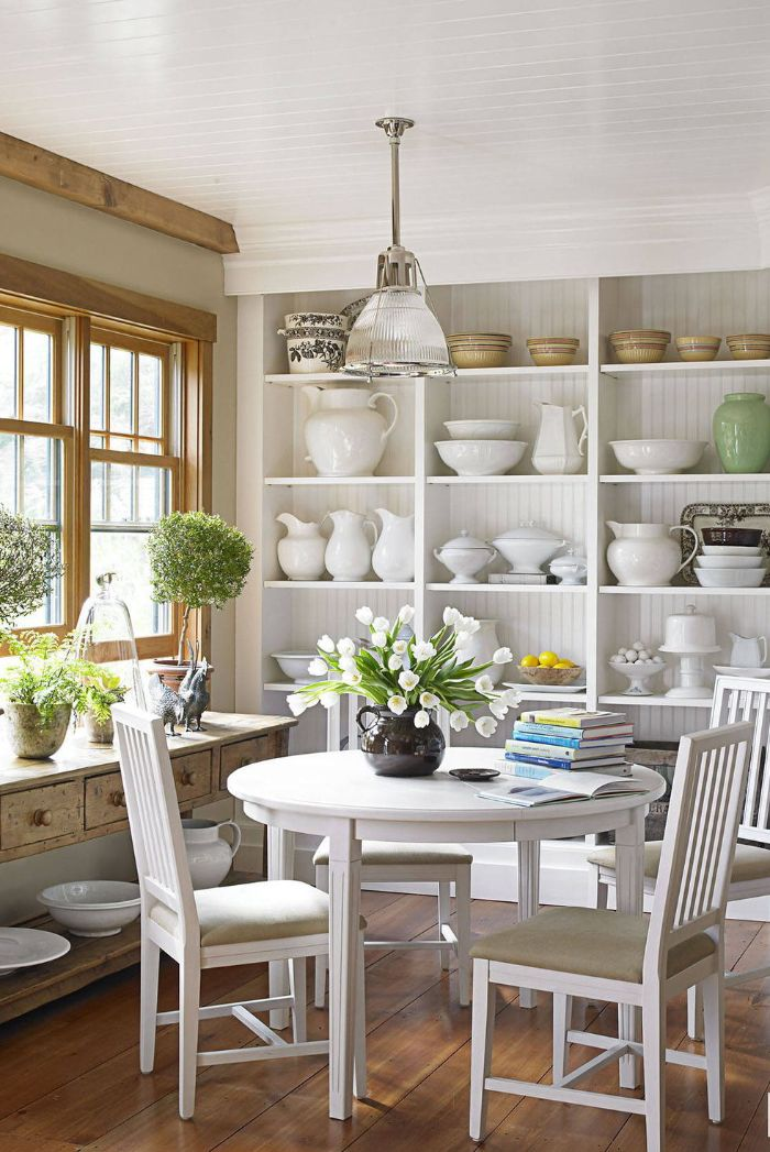 dining room with round table four chairs open shelving kitchen white backdrops bouquets of flowers