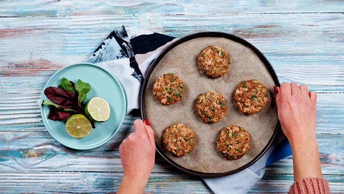 easy appetizers for a crowd six salmon meatballs arranged on paper lined baking tray placed on white wooden surface