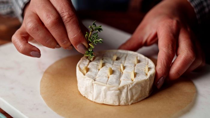 finger foods for party brie cheese sliced in the middle with garlic and rosemary placed in between the slits