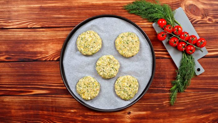 five zucchini fritters party snack ideas placed on paper lined baking tray placed on wooden surface