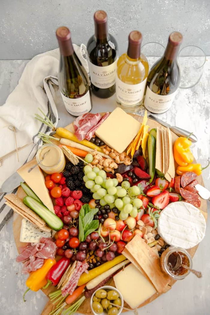 four bottles of wine next to round wooden board charcuterie board cheese meats fruits veggies crackers nuts