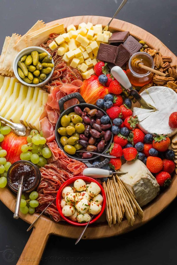 fruits cheeses meats condiments olives pickles charcuterie platter arranged on round wooden board