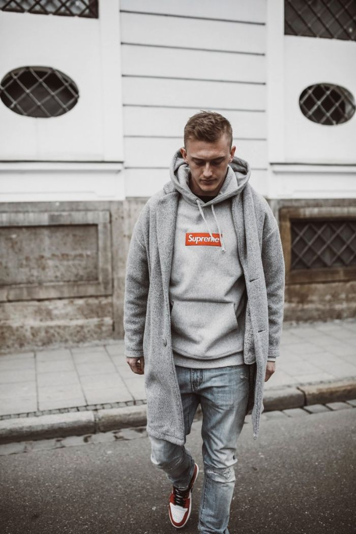 gray supreme hoodie with gray coat jeans nike air jordan ones in red black and white streetwear women man standing on the street