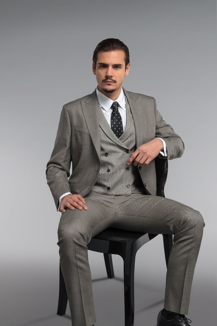 grisaille suit three piece suit worn with white shirt black tie by man sitting on black chair fabrics for suits