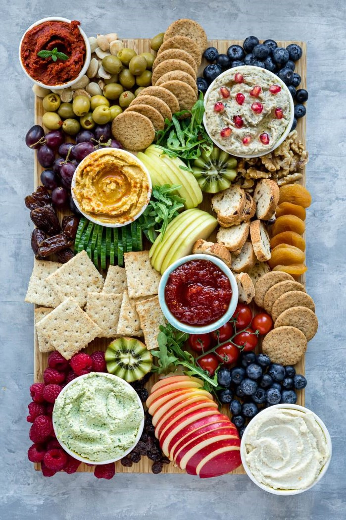 hummus olives veggies fruits crackers arranged on wooden tray what is charcuterie with condiments in bowls