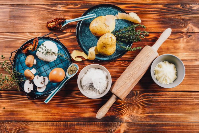 ingredients appetizer recipes potatoes mozzarella mushrooms egg herbs spread on wooden surface