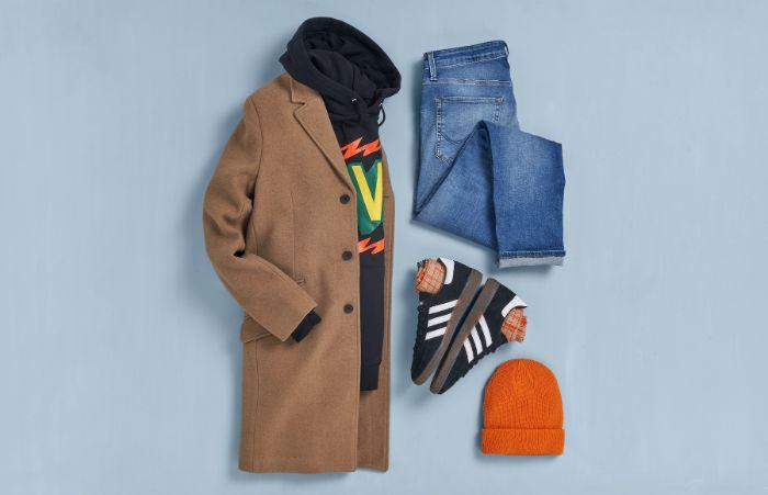 jeans black sneakers and hoodie beige coat orange beanie streetwear fashion blue background