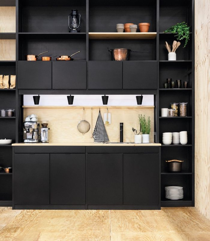 kitchen with black cabinets accents hanging kitchen shelves wooden backdrop and floor