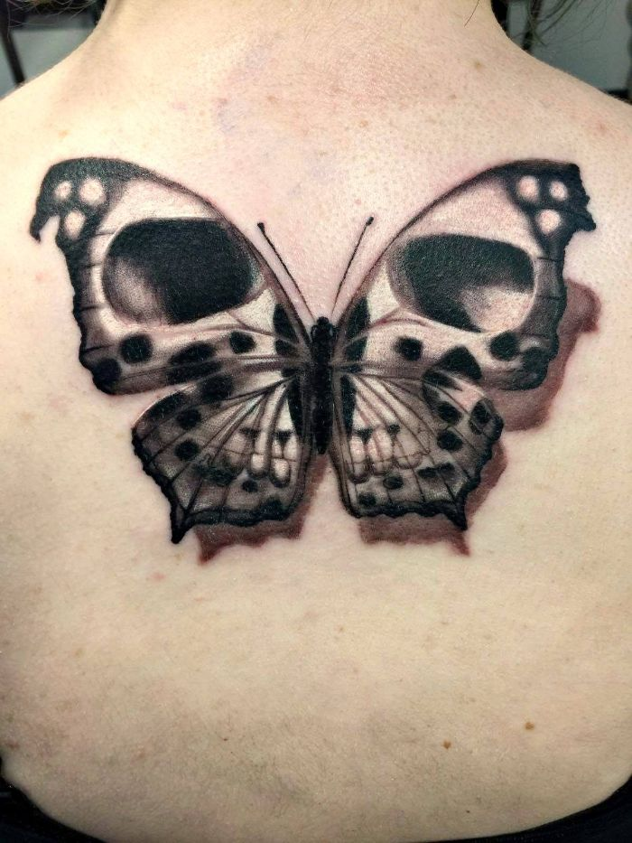 large back tattoo butterfly and flower tattoo black and white butterfly with skull like eyes