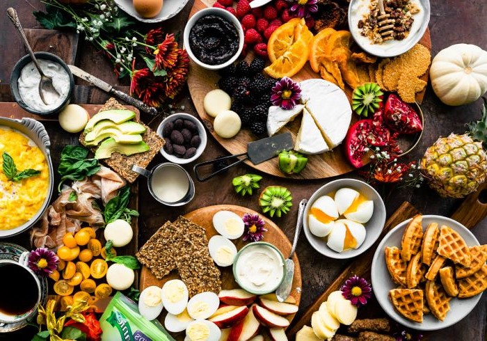 large wooden table covered with wooden boards meat and cheese board with crackers different types of fruits