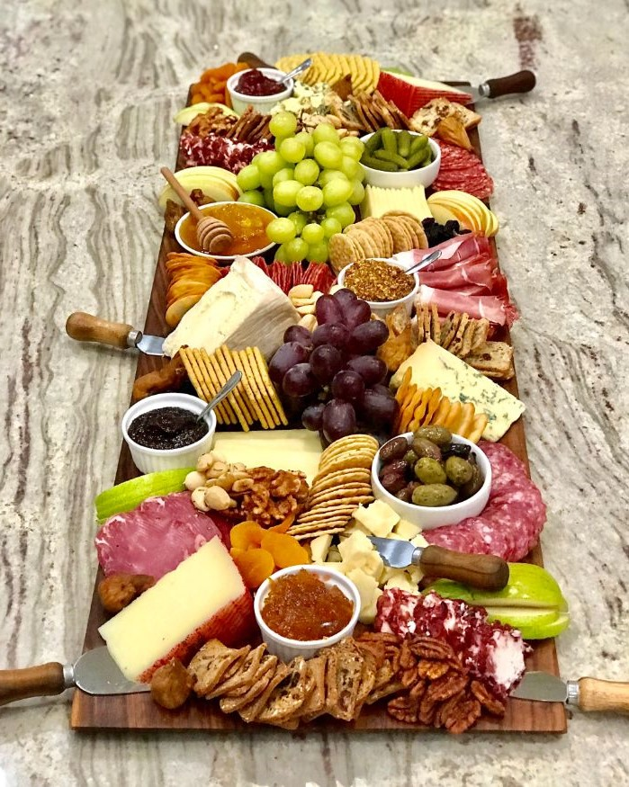long wooden board with different types of cheese meat what is a charcuterie board crackers fruits