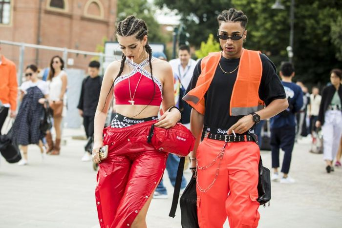 man and woman walking down the street mens streetwear red and orange leather pants red and black tops