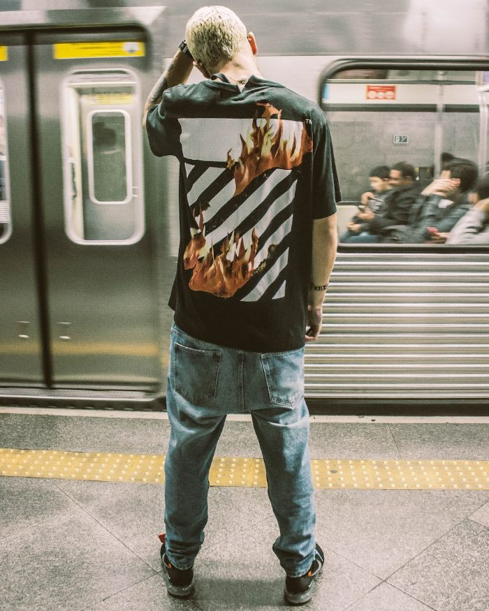 man wearing black off white t shirt jeans black sneakers streetwear fashion in the subway
