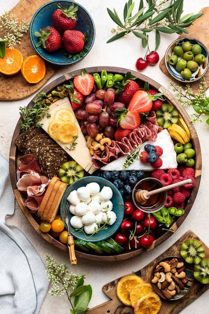 meat and cheese platter round wooden board covered with cheeses meats fruits veggies condiments