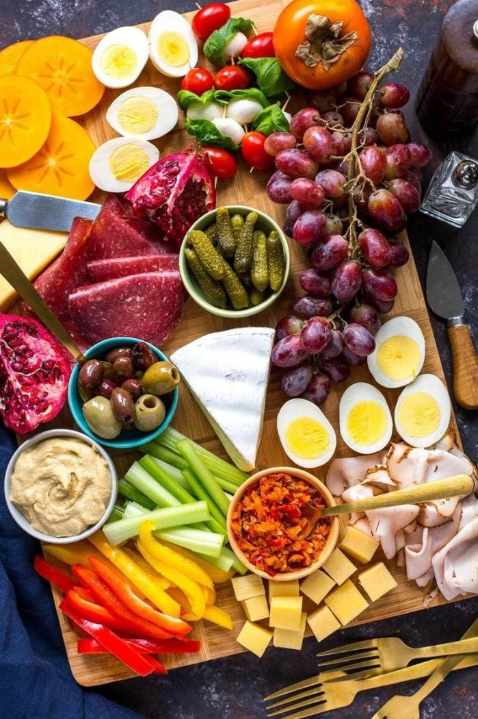 meat cheeses boiled eggs veggies fruits what is a charcuterie board arranged on wooden board