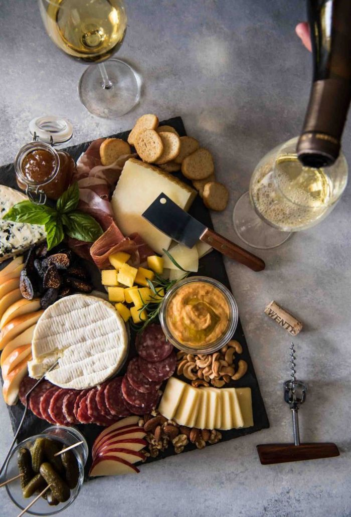 meats cheeses bread fruits nuts condiments arranged on black board what is a charcuterie board