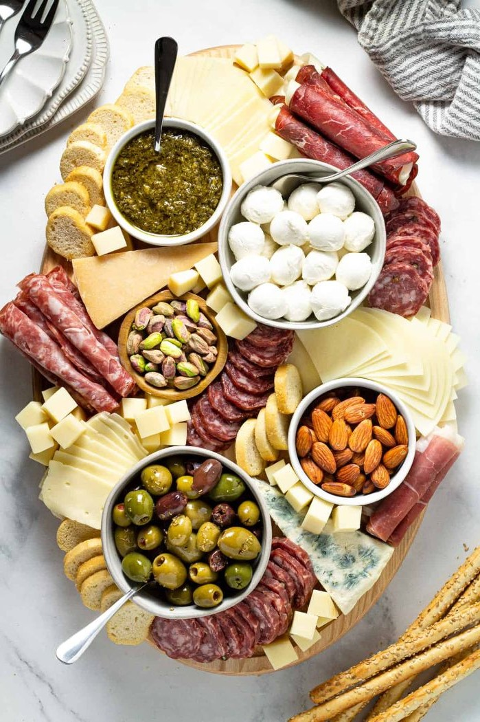 meats cheeses nuts olives bread how to make a charcuterie board arranged on elliptical wooden tray