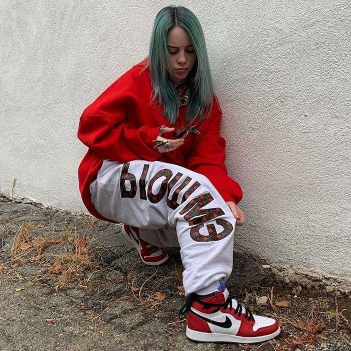 mens streetwear billie eilish wearing oversized red sweatshirt gray pants nike air jordan ones in red white black