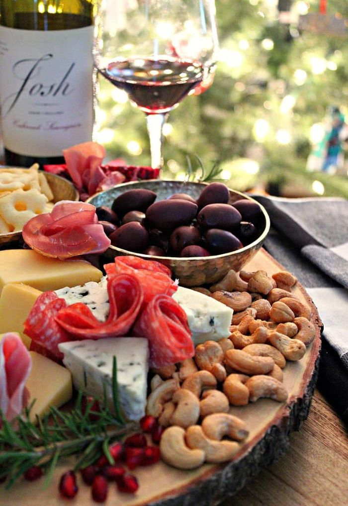 olives in a bowl meat and cheese board with nuts rosemary wine glass on the side