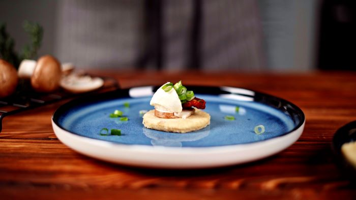 piece of potato dough with mushroom sun dried tomato mozzarella easy party appetizers placed on blue ceramic plate