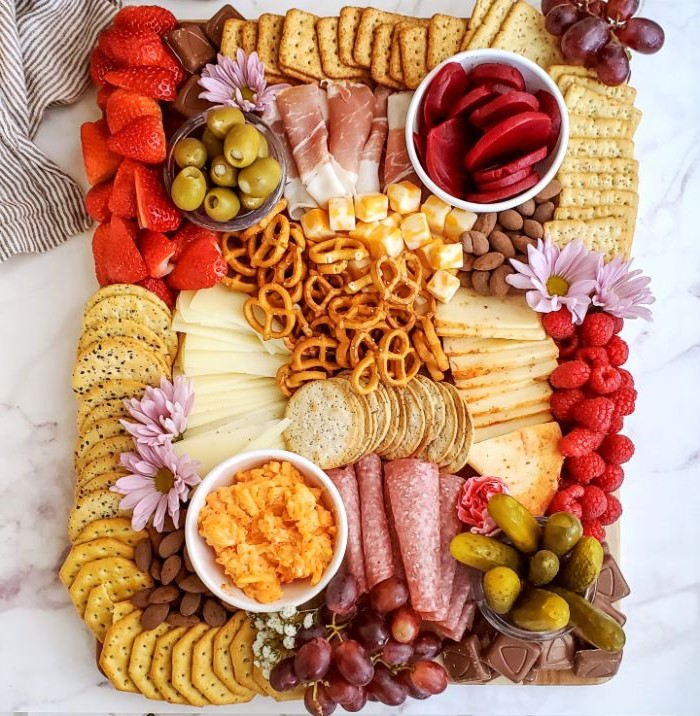pretzels crackers cheeses fruits pickles charcuterie platter chocolates purple flowers for decoration