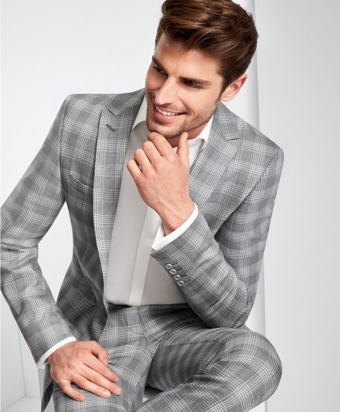 prince of wales light gray suit worn with white shirt fabrics for suits man sitting on a stool