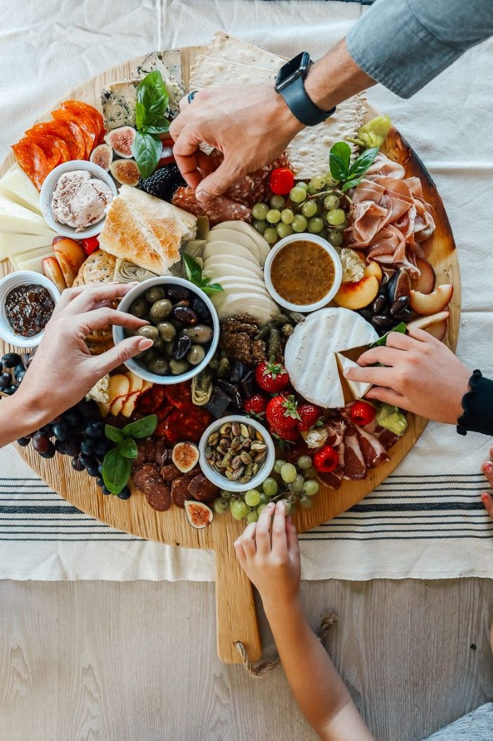 round wooden board charcuterie board ideas different types of cheese meat fruit veggies condiments