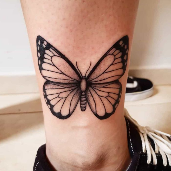 side of the ankle tattoo butterfly hand tattoo black and white butterfly on woman wearing black sneakers