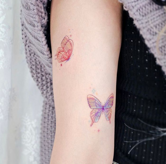 simple butterfly tattoo two butterflies in purple and orange forearm tattoo