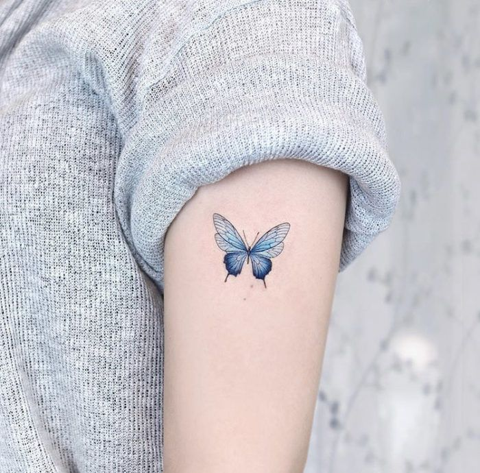 small blue butterfly on the side of the arm butterfly tattoos on shoulder on woman wearing gray sweater
