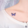 small blue butterfly under the collarbone butterfly tattoo woman wearing white blouse
