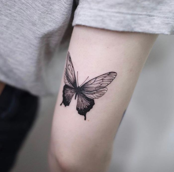 small butterfly tattoo on the back of the arm above the elbow in black and white