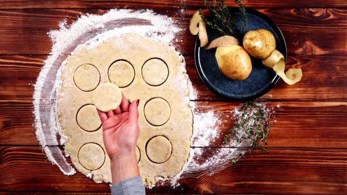 spread out potato dough on floured wooden surface easy party appetizers small round pieces cut out