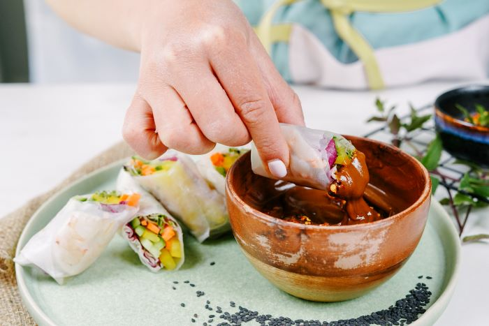 spring roll being dipped in sauce in wooden bowl easy appetizers for a crowd on ceramic plate