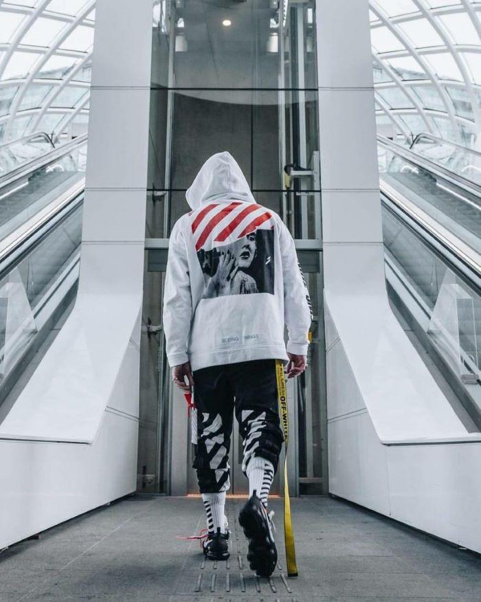 streetwear fashion man wearing all off white outfit white hoodie black pants black sneakers