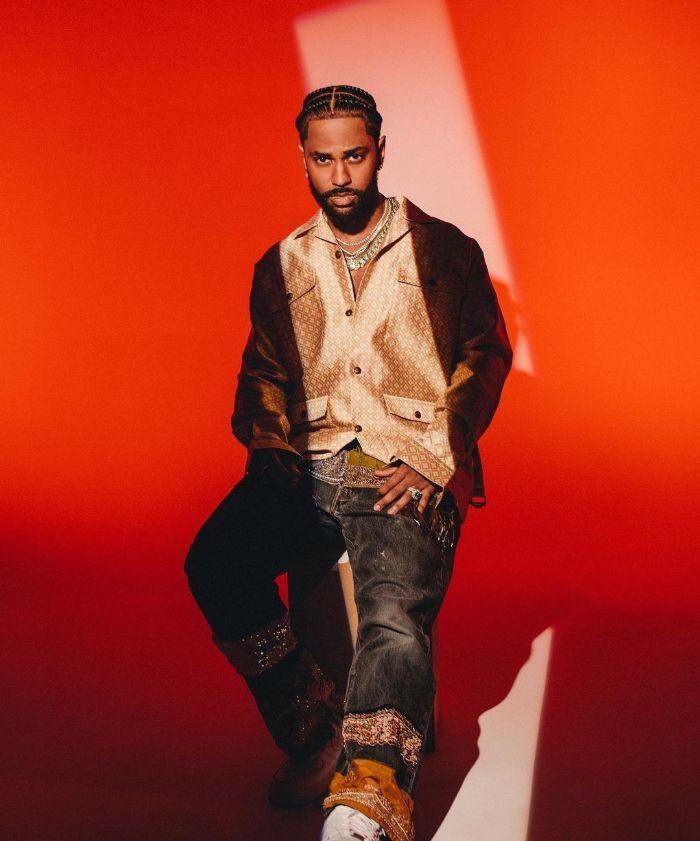 streetwear outfits big sean wearing jeans silk blazer sitting in front of orange backdrop
