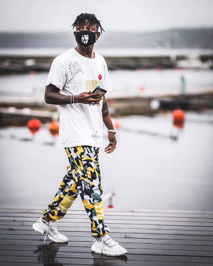 streetwear women man walking wearing white t shirt camouflage pants in black gray yellow white sneakers