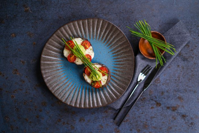stuffed mushrooms garnished with wild onion party snack ideas placed on ceramic bowl