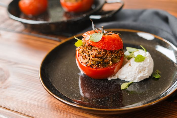 stuffed tomato with quinoa mixture appetizers for a crowd placed with ricotta cheese on black ceramic plate