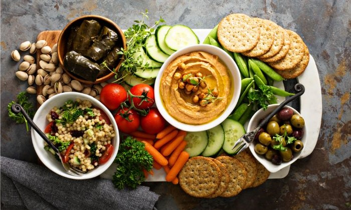 taboule salad hummus olives in bowls what is charcuterie crackers veggies nuts around them