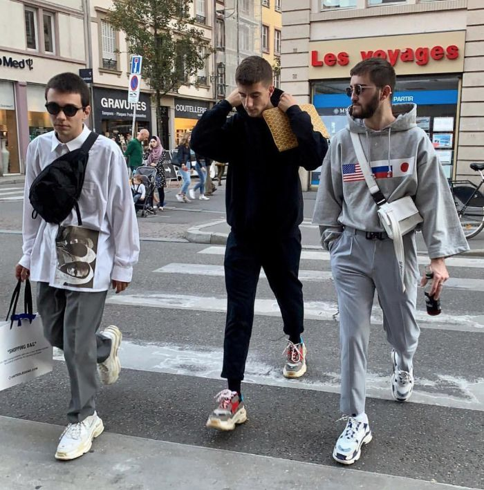three men walking down the street streetwear outfits wearing black and gray sweaters gray pants sneakers