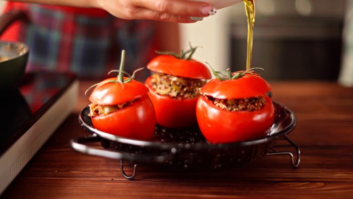tomatoes stuffed with quinoa mixture finger food appetizers placed on baking dish drizzled with olive oil