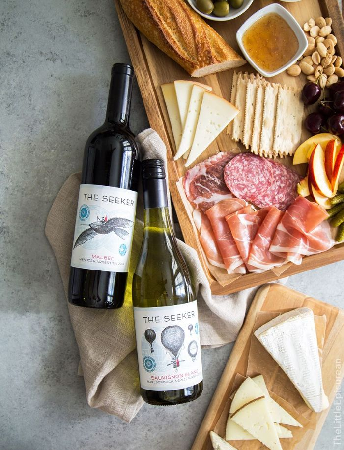 two bottles of wine placed next to wooden board meat and cheese board with baguette crackers fruits nuts