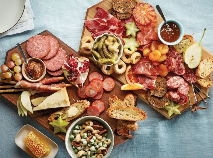 two separate charcuterie board with different types of meat cheese bread fruits honey and nuts